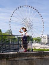 Femme Au Balcon Du Jardin Des Tuileries Avec La Grande Roue En Arrière Plan