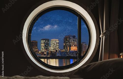 Okrągła rama okienna w sypialni w nocy z widokiem na miasto