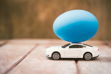 Easter Egg And Toy Car On Wooden Background,