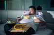 canvas print picture - Asian obese man eating junk foods before sleep