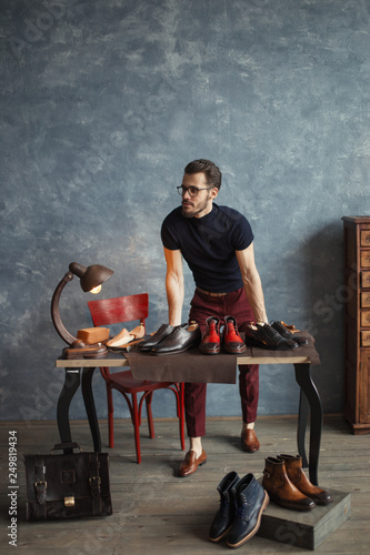 Photo  shoe designer offer his shoes to customers, full length photo
