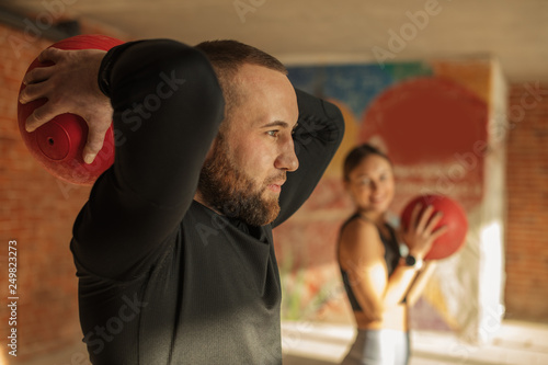 athletic sportsman and sportswoman doing exercises with medicine balls together in gym Fototapet