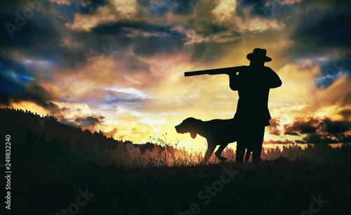 Obraz na plátně hunter with dog at sunset.