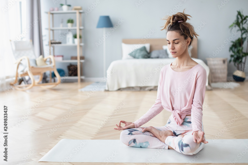 Fototapeta Portrait of attractive young woman working out at home, doing yoga exercise on white mat.
