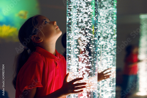 Obraz Child in therapy sensory stimulating room, snoezelen. Child interacting with colored lights bubble tube lamp during therapy session. - fototapety do salonu