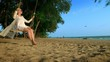 A happy blonde girl in a white dress and lace cape is swinging on a rope swing, on the beach by the sea.