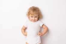 Caucasian Curly Baby Girl In A White T-shirt On A White Background Hands Holding A Waist. Child Hands In Hips