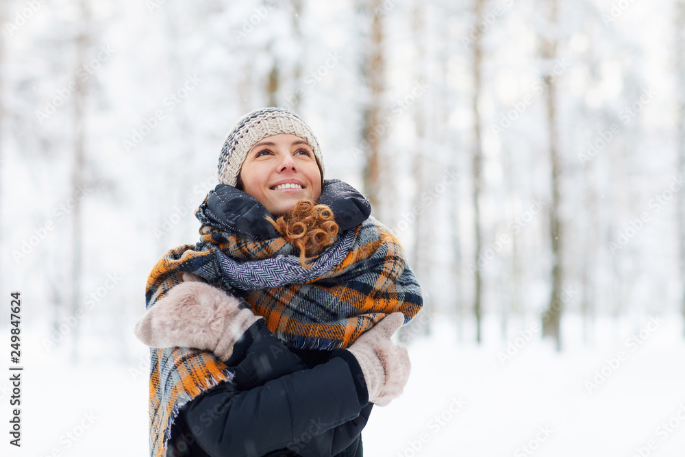 Fototapeta Waist up portrait of happy young woman in winter forest having fun and enjoying snow, copy space