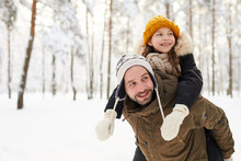 Portrait Of Happy Little Girl Riding On Fathers Back In Winter Forest Having Fun, Copy Space