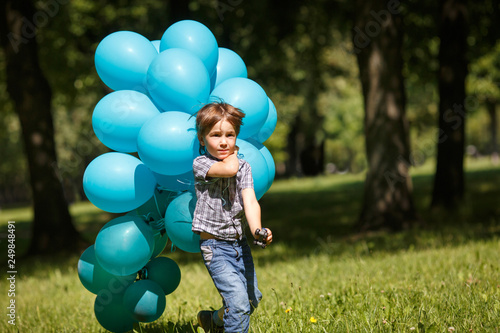 Fotografie, Obraz  A little boy runs in the park with a huge bunch of blue balloons.