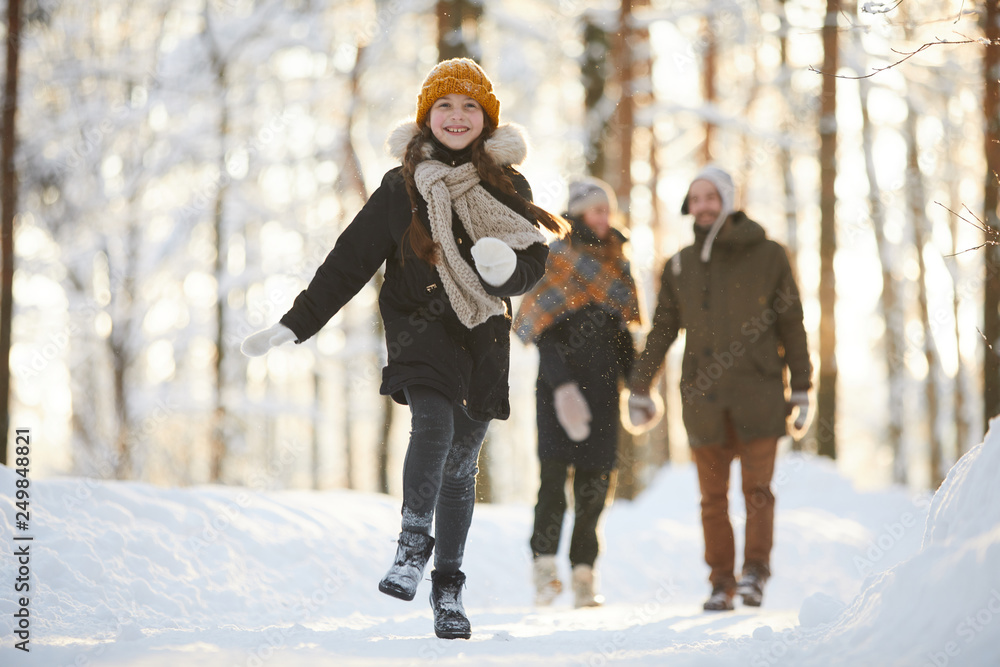 Fototapeta Full length portrait of happy little girl running towards camera in winter forest while enjoying walk with family, copy space