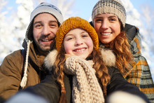 Closeup Portrait Of Happy Family Posing Looking At Camera In Beautiful Winter Forest