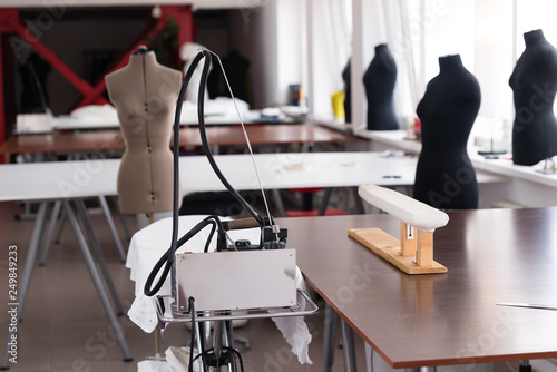 Fotografia  Tables for cutting fabric in the sewing workshop on the background of mannequins