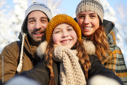 Obraz Closeup portrait of happy family posing looking at camera in beautiful winter forest - fototapety do salonu