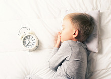 Kids Sleeping Concept With Asleep Little Boy In Bed With Alarm Clock