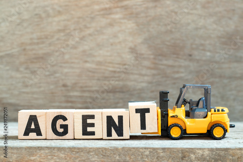 Toy forklift hold letter block t to complete word agent on wood background