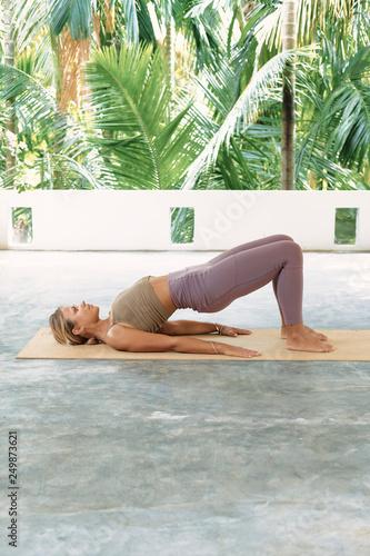 Fototapeta Woman Practicing Advanced Yoga on Organic Mat. Series of Yoga Poses. Tropical background obraz na płótnie