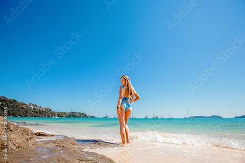 Poster Zanzibar Beautiful young woman with long hair in a blue swimsuit standing back in the sea and relax on the beach on Phuket, Thailand