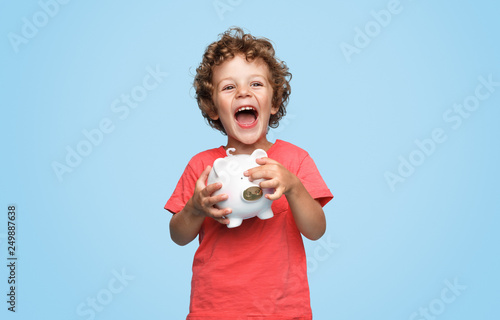 Excited boy with piggy bank