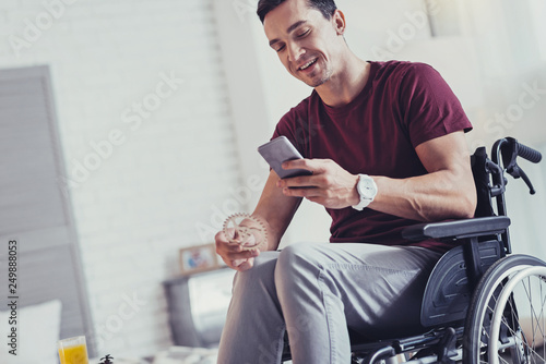 Valokuva  Positive disabled man using his smartphone