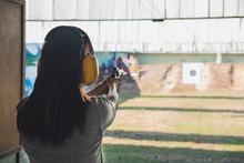 Young Woman Practice Gun Shoot...