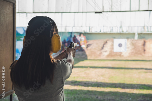 Obraz na płótnie Young woman practice gun shoot on target