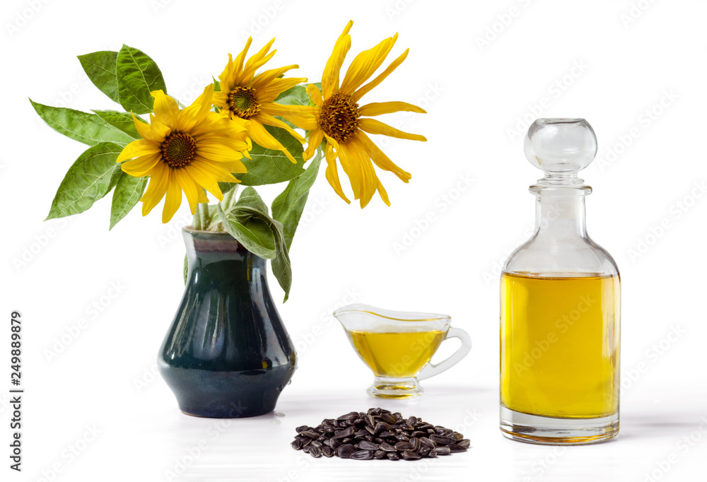 Fototapety, obrazy: Sunflower oil in a glass gravy boat and in a bottle, handful of sunflower seeds and a sunflower in a vase isolated on a white background.