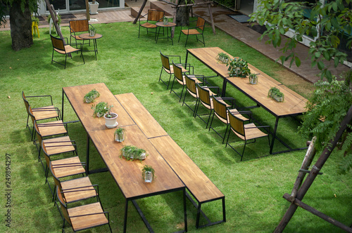 Fotografia Classic wood with steel rim tables and chairs are arranged in the little garden, shot from 2nd floor