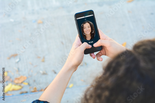 Photo Woman unlocking smartphone with facial recognition technology