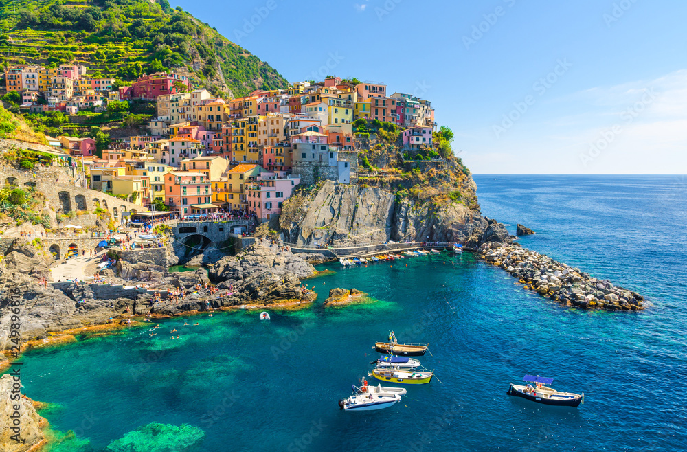 Fototapeta Manarola traditional typical Italian village in National park Cinque Terre, colorful multicolored buildings houses on rock cliff, fishing boats on water, blue sky background, La Spezia, Liguria, Italy