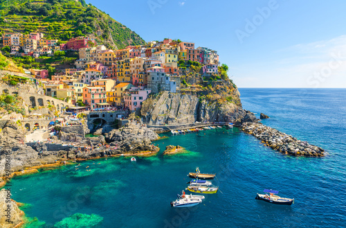 Türaufkleber Blau türkis Manarola traditional typical Italian village in National park Cinque Terre, colorful multicolored buildings houses on rock cliff, fishing boats on water, blue sky background, La Spezia, Liguria, Italy