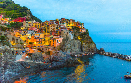 Aluminium Prints Europa Manarola traditional typical Italian village in National park Cinque Terre with colorful multicolored buildings houses on rock cliff and marine harbor, night evening view, La Spezia, Liguria, Italy