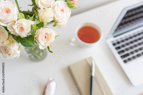 Fotografía  High angle view of pale pink roses in glass with home office desk in background