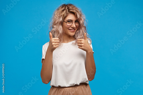 Obraz Cheerful hipster girl in trendy round eyewear making thumb up gesture with both hands and smiling joyfully, showing her support and respect to someone, saying Good job, Well done, I like that - fototapety do salonu