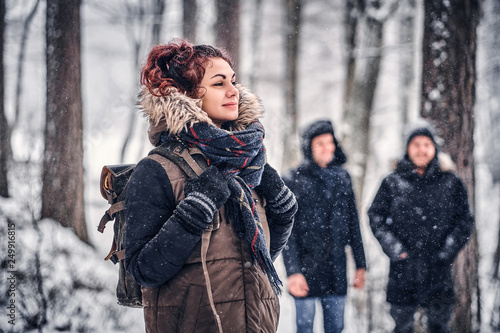 Portrait of a beautiful redhead girl with a backpack walking with his friends through a winter woods
