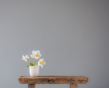 Three White Flowers In A Little Ceramic Vase On An Old Wooden Stool With Lots Of Copy Space