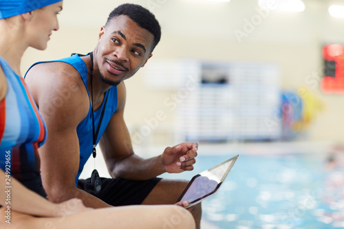 Portrait of handsome African-American fitness coach talking to client in swimmin Wallpaper Mural