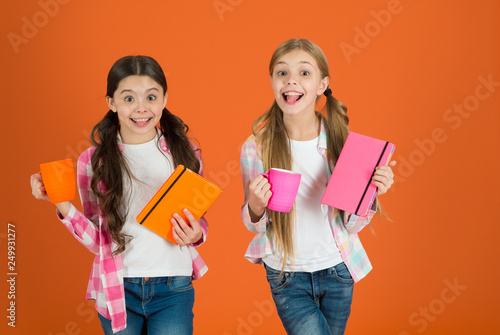 Fotografia  Girls kids with books and tea mugs orange background