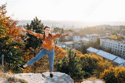Fotografia  Happy attractive girl have fun on sunset panorama of European city background