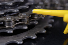 A Gear And Chain On A Workshop Table. Oiling And Repair Of Bicycle Drive.