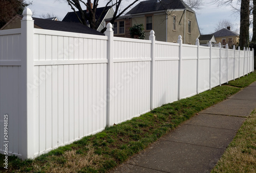 Tablou Canvas White vinyl fence in residential neighborhood.