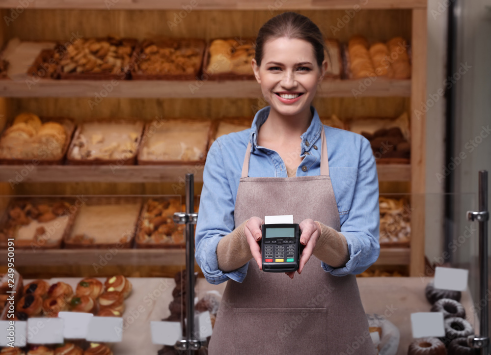 Fototapeta Seller holding payment terminal in bakery. Space for text