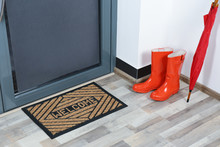 Rubber Boots, Umbrella And Mat Near Door In Hallway
