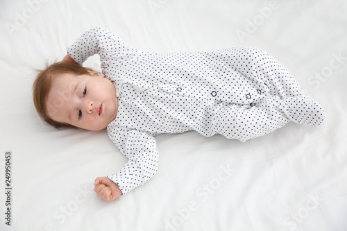 Valokuvatapetti Adorable baby in cute footie on white sheet, above view