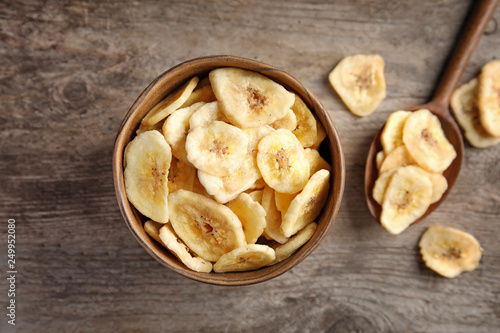 Obraz na plátně Bowl and spoon with sweet banana slices on wooden table, top view