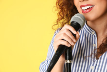 African-American Woman Singing In Microphone On Color Background, Closeup View With Space For Text