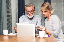 Senior Couple Reading Documents And Calculating Bills To Pay In Living Room At Home.Retirement Couple And Loan Bankruptcy Money Concept