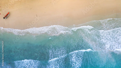 Aerial : Overhead view at empty sand beach line ,waves breaking against the coast