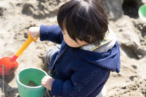 Fotografie, Obraz  砂場で砂遊びする子供