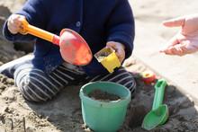 砂場で砂遊びする子供